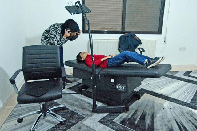 7d16ed21a5d120 A child is being prepped to receive Sensori-motor Auditory Visual Education  at the newly opened American Centre for Autism in Amman. The one-hour  treatment ...
